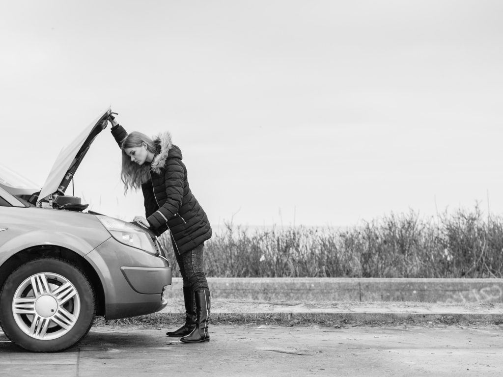 woman opening the hood of a car and looking at the engine