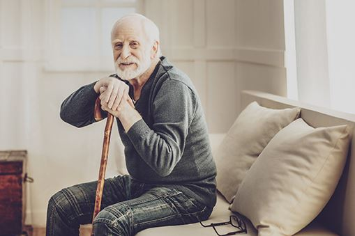 Elderly Man Sitting on a Couch Holding a Cane
